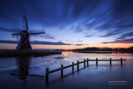 Traditional, Dutch windmill at a lake during an cold sunset in winter.