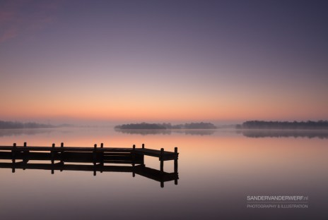 Jetty during a tranquil, foggy dawn at a lake.