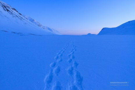 Footprints in the fresh snow on an evening in the mountains.