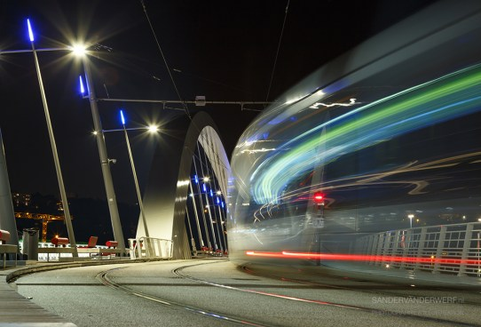 Tram speeding over a bridge at night