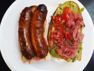 Homemade Argentine chorizo with onion curtido, chimichurri, guacamole, and tomato/onion curtido on baguette