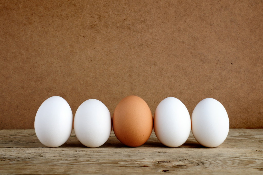 One brown egg among white eggs on wooden table