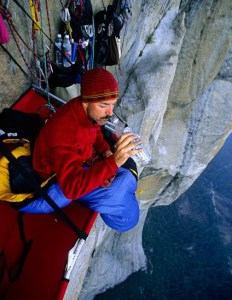 """Kevin Brown drinks water near the end of a multi-day ascent of El Capitan in Yosemite Valley in 2003.  The Big Wall route called """"Excalibur"""" is rated grade VI 5.8 A3. (Photo by Kevin Steele/Aurora)"""