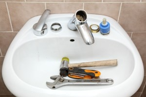 Water tap ceramic cartridge valve and plumber tools in a bathroom