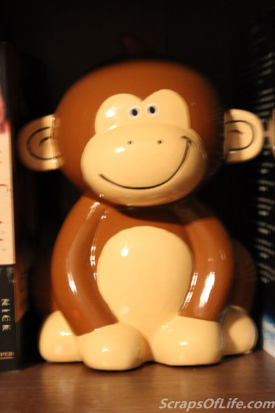 A cheeky little monkey bank serves as a bookend (or, really, a book middle, separating two subjects on one shelf).