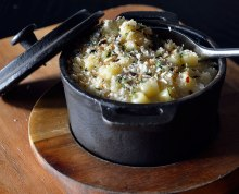 mac and cheese in cast iron pot on a wooden board