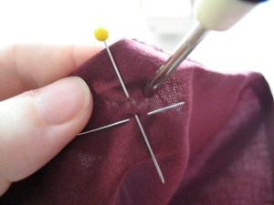 Figure out where you'd like your eyelet.  Poke the Awl through the fabric.