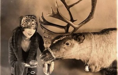 "Myrna Loy, before gaining ""Thin Man"" fame, feeds one of Santa's reindeer, 1920's."