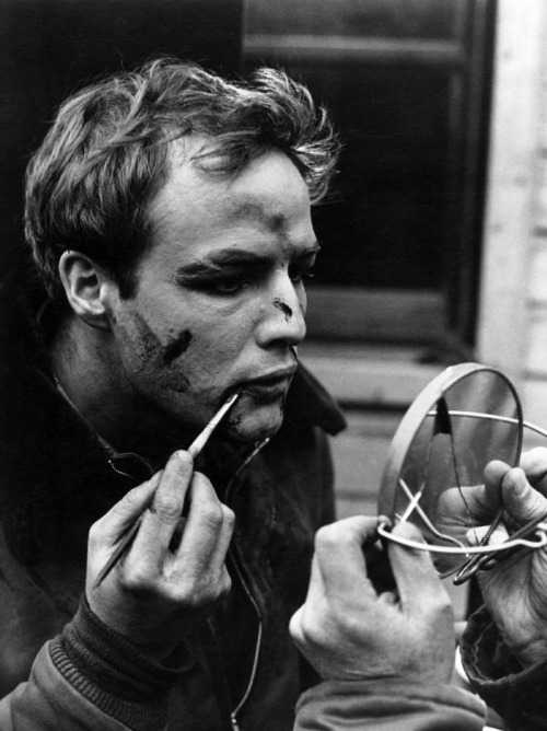 "Marlon Brando applying his make-up on the set of On the Waterfront (1954, dir. Elia Kazan) ""[In On the Waterfront] there was a scene in a taxicab, where I turn to my brother, who's come to turn me over to the gangsters, and I lament to him that he never looked after me, he never gave me a chance, that I could have been a contender, I coulda been somebody, instead of a bum…It was very moving. And people often spoke about that, 'Oh, my God, what a wonderful scene, Marlon, blah blah blah blah blah.' It wasn't wonderful at all. The situation was wonderful. Everybody feels like he could have been a contender, he could have been somebody, everybody feels as though he's partly bum, some part of him. He is not fulfilled and he could have done better, he could have been better. Everybody feels a sense of loss about something. So that was what touched people. It wasn't the scene itself. There are other scenes where you'll find actors being expert, but since the audience can't clearly identify with them, they just pass unnoticed. Wonderful scenes never get mentioned, only those scenes that affect people."" -Brando, quoted in Lawrence Grobel's Conversations with Brando (1993)"