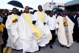 Clergy following the hearse that carried Father Jean-Justes body on the June 6 funeral walk include Father Reginald, far right, walking arm in arm with a parishioner. He gave the only memorable sermon during the wake on Friday, June 5, denouncing the hypocrisy of those who persecuted Father Jean Juste, yet now cant rush to the frontlines fast enough to praise him at his funeral in order to leverage his reputation in the community for their own political capital.  Photo: Norluck Dorange