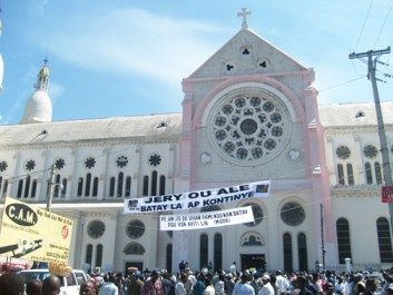 "A large banner in front of Haiti's national cathedral reads, ""[Father] Jery, you left us but the struggle continues."" – Photo: ©2009 Jean Ristil, Haiti Information Project"