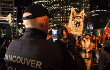 Police videotape Olympic Resistance Network protesters in downtown Vancouver, B.C., Feb. 12, 2009, exactly one year before the opening of the 2010 Winter Olympics in Vancouver and Whistler. Military and police flanked by helicopters rehearsed maneuvers in Vancouver, where escalating harassment, intimidation and surveillance of activists had already begun. Photo: The Blackbird