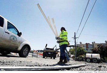 Carolena Williams removes concrete forms on a road improvement project at the entrance to the Hunters Point Shipyard. She is a rarity. Black construction workers have been an endangered species in San Francisco since the Black contractors who used to keep them working were run out of business in 1998. – Photo: Lance Iversen, SF Chronicle