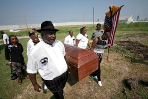 "In the Lower 9th Ward, the heart of New Orleans' Black culture, ""cleansed"" post-Katrina of its people denied the rebuilding funds they were entitled to, tenacious residents hold a memorial ceremony on Aug. 29, 2008, the third anniversary of the storm, the coffin symbolizing its victims. – Photo: Lee Celano, Reuters"