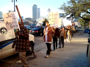 "Protesters marched outside the NOPD station Thursday morning, Jan. 8, with signs that demand ""Justice for Adolph Grimes III"" and ""Self-Determination for the African-American Nation."" At the same time in Oakland, California, protesters packed the BART board meeting to demand justice for Oscar Grant, another 22-year-old Black father executed by police in the early hours of New Year's Day. – Photo: Darwin Bond-Graham"