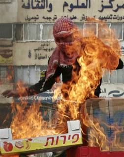 "An Israeli Palestinian burns Israeli produce boxes during a protest. ""Whenever Israel has been in conflict with its neighbors, the allegiances of its Arab citizens have been tested, and their empathy has often been with the other side,"" according to the New York Times Jan. 19. ""But this war was worse, they say, because it was waged against their own people and they were watching it as it happened. More prosperous, educated and 'Israeli-fied' than their kin in the West Bank and Gaza, the Israeli Arabs are becoming more Palestinian at the same time. The feelings of estrangement could last long after the Gaza war."" – Photo: AP"