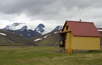 Roger stands in the entrance of our second hut, Þjófadalir, nestled into a little valley.
