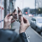 Punk guy looking at himself in a shattered mirror in the city streets