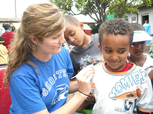 Shorter student doing face painting