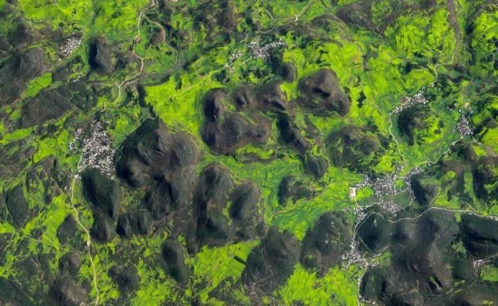 Campos de flores de Canola cobrem a paisagem montanhosa de Luoping County, China, 19 de março de 2015. (Daily Overview)