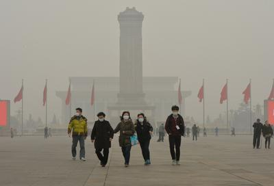 Chinese tourists wear facemasks during a visit to Tiananmen Square as heavy air pollution shrouds Beijing.(Photo: AAP)
