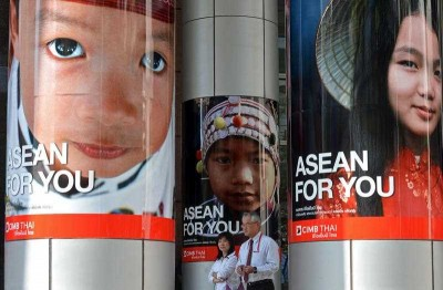 Thai office workers walk past advertising promoting the ASEAN Economic Community in Bangkok on 13 January 2013. The AEC is unlikely to be ready by its deadline. (Photo: AAP)