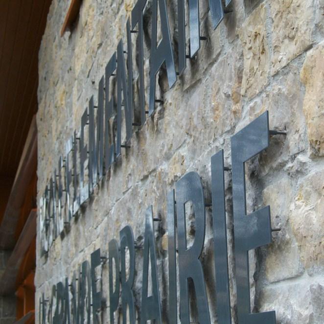 Enseigne lettres découpées en alu laqué fixées par goujons