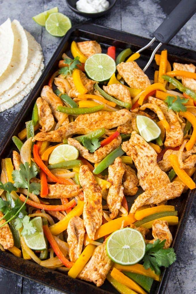 Sheet Pan Chicken Fajitas- Let the oven do the work! Only one sheet- pan and about 20 min needed to have tasty chicken fajitas on your table. Perfectly seasoned juicy chicken, bell peppers, and caramelized onions nestled in soft flour tortillas and topped with a squeeze of fresh lime and a sprinkling of fresh cilantro. A perfect weeknight meal the whole family will love.