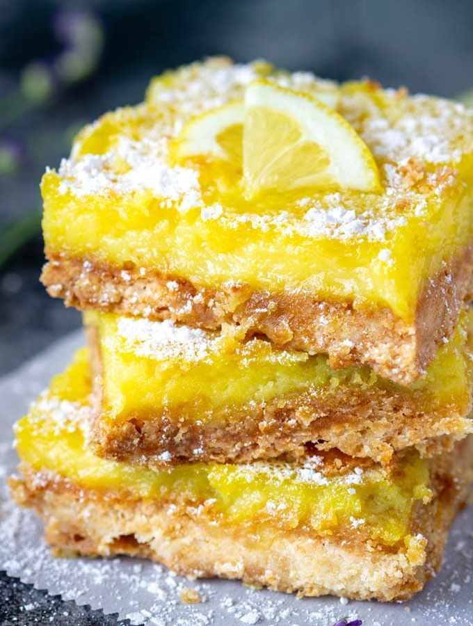 Healthier Lemon Bars- Indulge your sweet tooth! These easy to make Lemon bars have a golden buttery shortbread crust and a custard like filling with the perfect blend of sweetness and bright lemon flavor. The best part? These Weight Watchers Lemon bars are only 100 cal/each (5 Smart pts) .