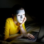 Anonymous teenager in mask on internet at night. Photo via Getty Images.