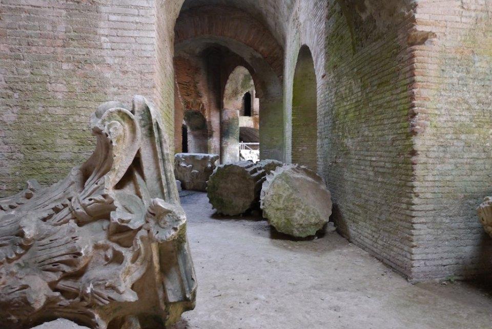 Backsteingewölbe des Amphitheaters von Pozzuoli. Im Vordergund liegt ein römisches Kapitell
