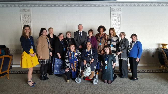 Group photo with women standing, one wheelchair user and one man in the back row.