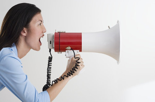 A woman shouting with a megaphone, promoting her brand