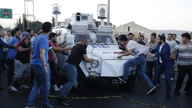People try to stop a Turkish police armoured vehicle carrying soldiers that participated in the coup and surrendered on ...