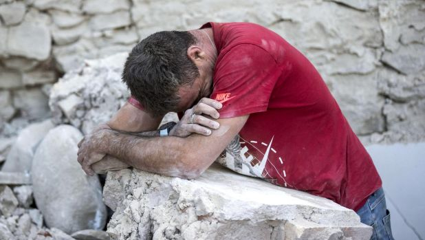 A man leans on rubble following an earthquake in Amatrice.