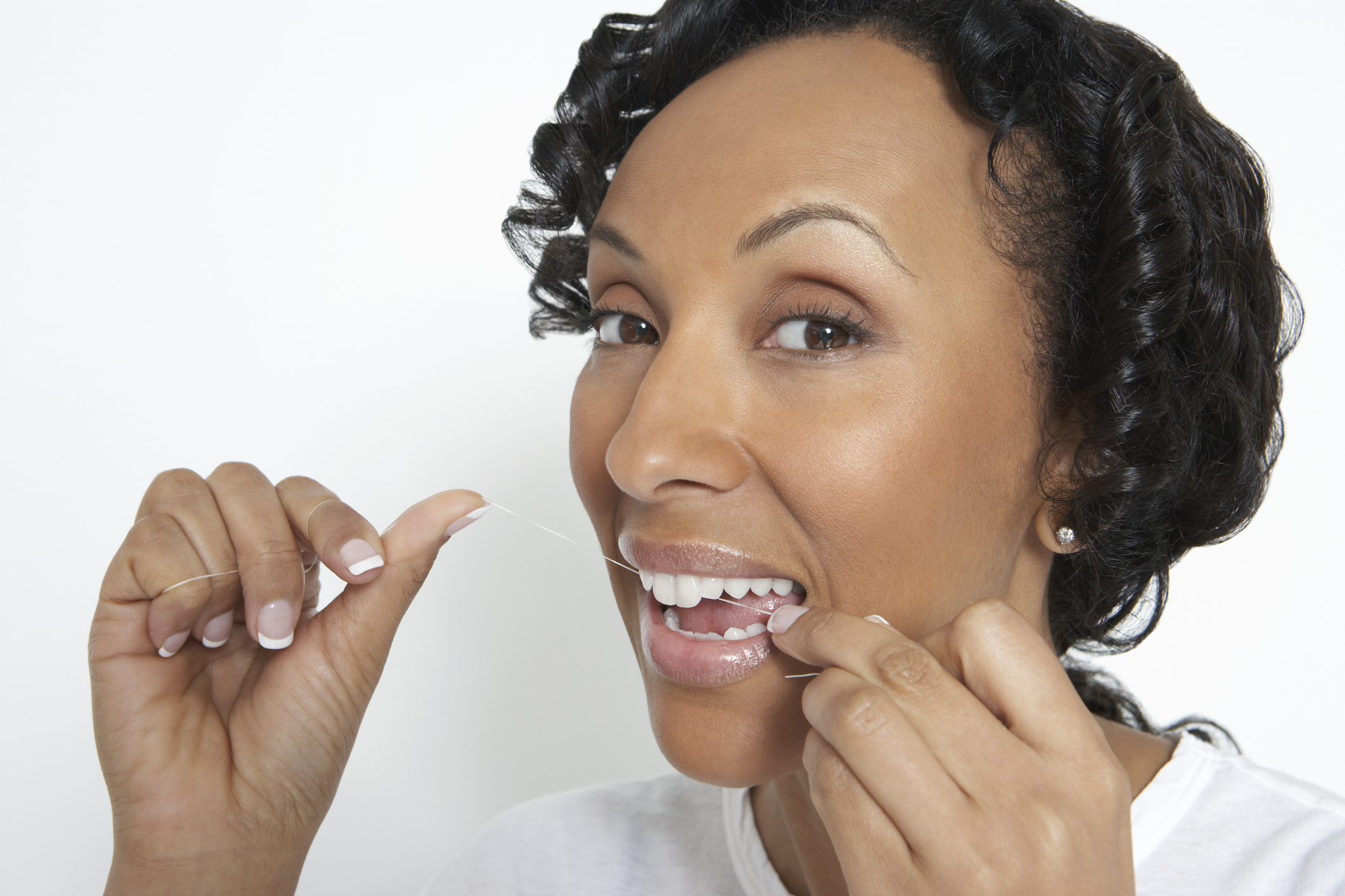 Woman flossing teeth, studio shot