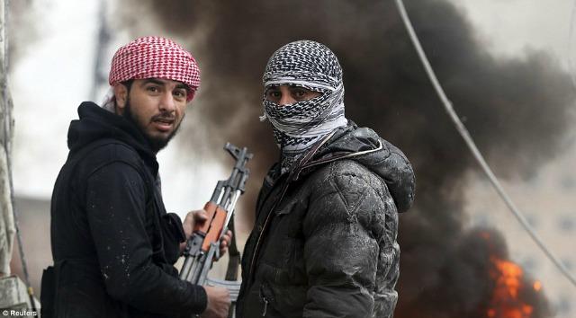Dos combatientes sirios ofrecen un momento fotográfico en medio del combate.