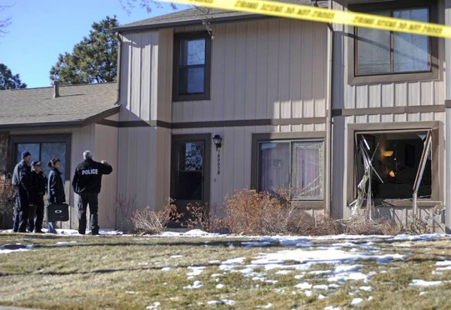 Police survey the outside of a townhouse complex following an overnight hostage-taking incident in Aurora
