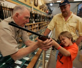 McConathy holds a hunting rifle with a short stock at the Cabela's store in Fort Worth