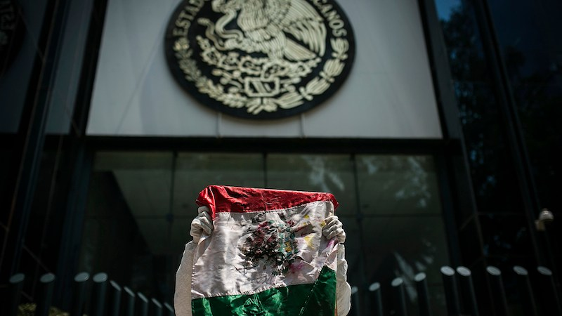 MEXICO CITY, MEXICO - JUNE 26: A man of the Arte Accion Cero12 artistic group, holds a Mexican flag during the protest as part of the UN's International Day in Support of Victims of Torture at Attorney General of Mexico on June 26, 2015 in Mexico City, Mexico. (Photo by Manuel Velazquez/LatinContent/Getty Images)