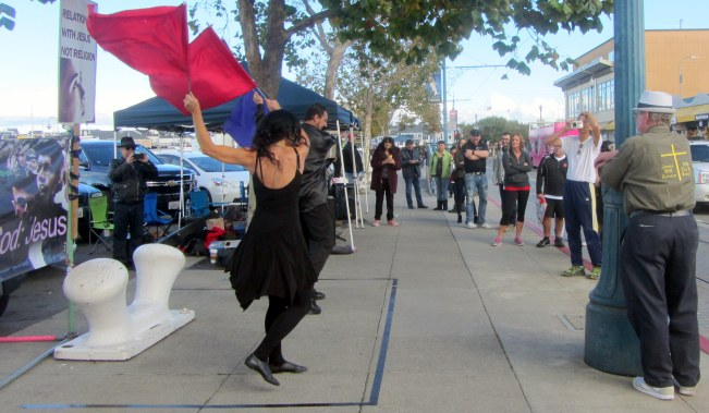 Jeff and Alina Parrott dance with flags at Fisherman's Wharf.