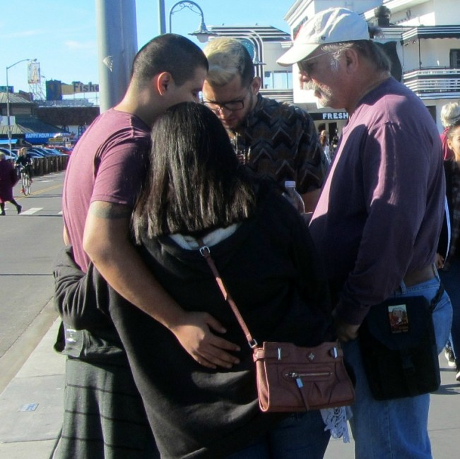 JACOB AND STEVE PRAY WITH COUPLE AT 5TH AND MARKET.