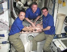 Commander Mike Fossum (center) and Flight Engineers Sergei Volkov (right) and Satoshi Furukawa attach the Expedition 29 patch inside the station. (Credits: NASA)