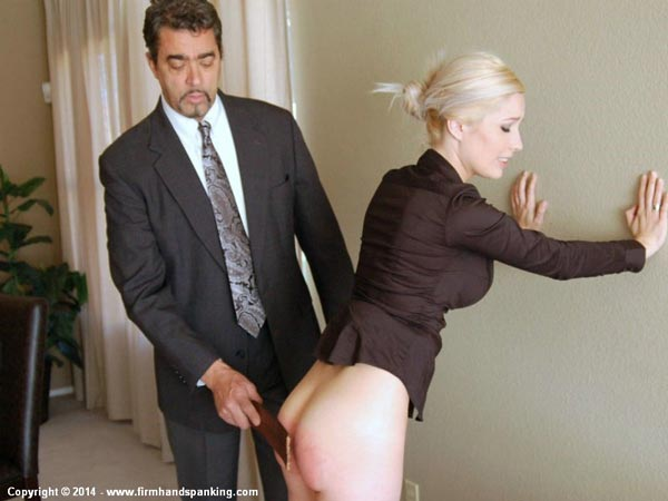 Intern Tara Somerville bends over and leans against the wall for a bare bottom strapping