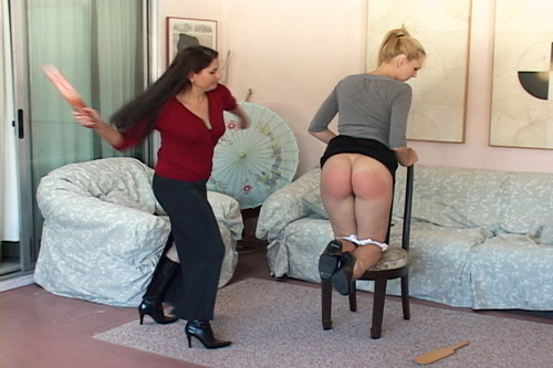 Chelsea swings the leather strap at poor Amelia's bottom with force