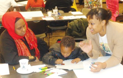 DeVon Nolen (at right) with son, speaking to attendee at  October 29 TCRC proposal meeting