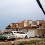 tornado damage to a house, cars