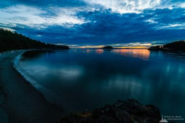 A long exposure landscape photograph of the July sunset over the water along North Beach at Deception Pass State Park, Washington.