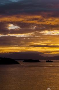 A landscape photograph of a Summer sunrise over Fidalgo Bay as viewed from Cap Sante Park in Anacortes, Washington.
