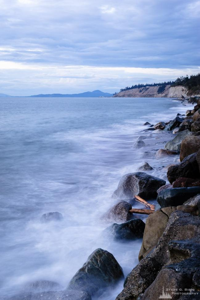 A long exposure photograph of the waves crashing against the rocky shoreline at the Hastie Lake Road Boat Launch on the Western coast of Whidbey Island, Washington.
